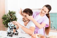 Un uomo raccoglie un robot nella cucina La sua amica è venuto a lui da dietro e delicatamente la copre occhi di sue mani Fotografie Stock