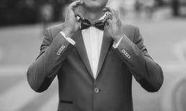 Un uomo regola la sua cravatta a farfalla Fotografia Stock Libera da Diritti