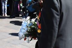Un uomo in rivestimento con gli ordini e medaglie sul suo petto che tiene un mazzo dei fiori bianchi fotografia stock