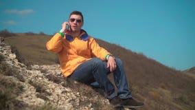 Un uomo in rivestimento giallo, blue jeans e vetri si siede in montagne, gode del paesaggio, parlando sul telefono, ridente stock footage