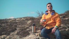 Un uomo in rivestimento giallo, blue jeans e vetri si siede nelle montagne, gode del paesaggio, beve il t? da un termos stock footage