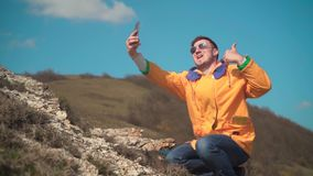Un uomo in rivestimento giallo, blue jeans e vetri si siede nelle montagne, gode del paesaggio, prende un selfie, fotografie video d archivio