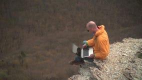 Un uomo in rivestimento giallo, blue jeans e vetri si siede sull'orlo di una scogliera e lavora ad un computer portatile video d archivio