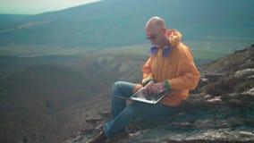Un uomo in rivestimento giallo, blue jeans e vetri si siede sull'orlo di una scogliera e lavora ad un computer portatile archivi video