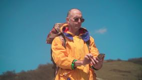 Un uomo in rivestimento giallo e vetri sta in montagne, godendo del paesaggio ed è guidato dalla mappa nel telefono archivi video