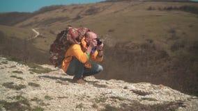 Un uomo in rivestimento giallo e vetri sta stando in montagne, sta godendo del paesaggio e sta facendo le foto sulla macchina fot archivi video