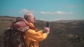 Un uomo in rivestimento giallo e vetri sta stando nelle montagne, sta godendo del paesaggio e sta facendo le foto sul telefono archivi video