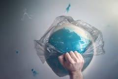 Un uomo rompe una borsa di immondizia che ? globo avvolto di pianeta Terra Il concetto di ecologia ed inquinamento del circondare immagine stock