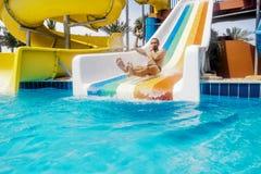 Un uomo rotola giù una collina in un aquapark Immagine Stock
