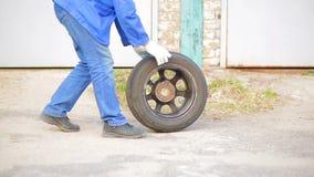 Un uomo rotola una gomma di automobile con un disco su asfalto stock footage