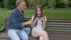 Un uomo ruba una borsa da una borsa del ` s della ragazza Chiede di aiutare il suo sguardo allo smartphone Attualmente, l'altra m archivi video