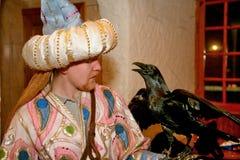 Un uomo saggio favoloso meravigliosamente si è vestito in seta Derviscio orientale, uno scienziato con la mano nera Raven Fotografia Stock