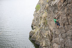 Un uomo scala sulla roccia vicino all'acqua fotografia stock libera da diritti
