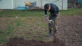 Un uomo scava la terra con una pala stock footage