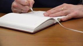 Un uomo scrive in un diario video d archivio