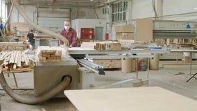 Un uomo sega gli spazii in bianco di legno sulla macchina, la produzione della porta delle porte interne del villaggio stock footage