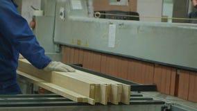 Un uomo sega gli spazii in bianco di legno sulla macchina, la produzione della porta delle porte interne del villaggio video d archivio