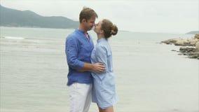 Un uomo segna una ragazza dai capelli, la abbraccia e bacia Una coppia gli amanti riposa sul mare stock footage