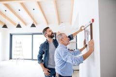 Un uomo senior che aiuta suo figlio che appende sulle immagini sulla parete, un nuovo concetto domestico immagine stock libera da diritti