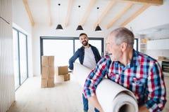 Un uomo senior che aiuta suo figlio con fornire nuova casa, un nuovo concetto domestico immagine stock
