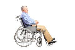 Un uomo senior disabile che posa in una sedia a rotelle Fotografie Stock Libere da Diritti