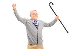 Un uomo senior felice che tiene una canna e che gesturing felicità Fotografie Stock Libere da Diritti