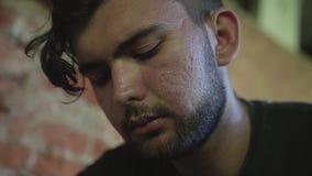 Un uomo senza tetto con gli sguardi tristi e tristi del fronte alle vecchie foto è situato in una costruzione abbandonata archivi video