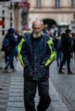 Un uomo senza tetto coperto dentro sbava e la sporcizia cammina tramite le vie di Praga un giorno di molla freddo immagine stock