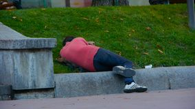 Un uomo senza tetto dorme su un prato inglese sul bordo della strada, lungo cui la gente cammina, sonni ubriachi di un uomo sull' archivi video