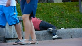 Un uomo senza tetto dorme su un prato inglese sul bordo della strada, lungo cui la gente cammina, sonni ubriachi di un uomo sull' video d archivio