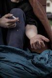 Un uomo senza tetto prende le droghe immagine stock