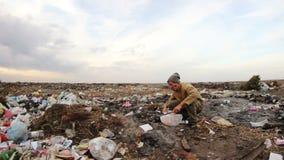 Un uomo senza tetto si siede sui rifiuti e mangia il pane stock footage