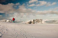 Un uomo si arrampica su un pendio della neve Fotografia Stock Libera da Diritti