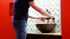 Un uomo si lava le sue mani in un lavandino con una progettazione rara migliorata video d archivio
