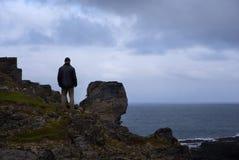 Un uomo si leva in piedi su una roccia sul litorale artico Fotografie Stock Libere da Diritti