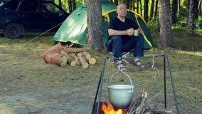 Un uomo si siede ad una tenda, beve il tè e guarda un giocatore di bocce appendere sopra un fuoco stock footage