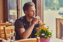 Un uomo si siede alla tavola in un caffè Immagini Stock Libere da Diritti