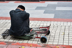 Un uomo si siede da solo sul piedistallo Immagine Stock