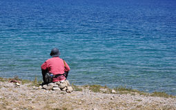 Un uomo si siede dal lago Fotografie Stock Libere da Diritti