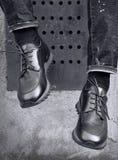Un uomo si siede e le sue gambe appendono in scarpe da tennis di cuoio alla moda Immagine Stock