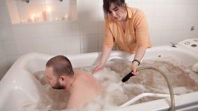 Un uomo si siede negli oli da bagno medicinali, un impiegato della ragazza ad una stazione termale, ottenente un massaggio dall'a stock footage