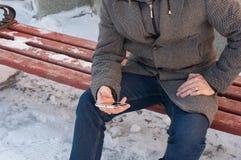 Un uomo si siede su un banco e sull'esame del telefono Immagini Stock