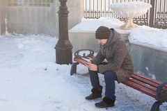 Un uomo si siede su un banco e sull'esame del telefono Fotografie Stock