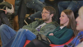 Un uomo si siede su un cuscino e sorride durante la prestazione comica archivi video