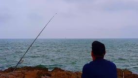 Un uomo si siede su una roccia e guarda fuori al mare archivi video