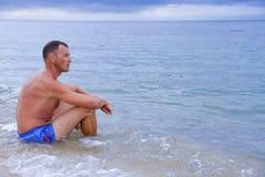 Un uomo si siede sulla riva di mare Immagini Stock Libere da Diritti