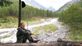 Un uomo si siede vicino ad un fiume al di nuovo ad un albero immagine stock