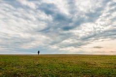 Un uomo solo che cammina sull'orizzonte del paesaggio Fotografia Stock