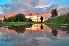 Un uomo solo e una linea elettrica ad alta tensione - linee elettriche riflesse Fotografie Stock Libere da Diritti