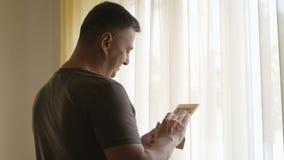 Un uomo solo in una maglietta cachi ha fatto una pausa la finestra, tenente un'immagine nel telaio di legno L'uomo esamina la fot stock footage
